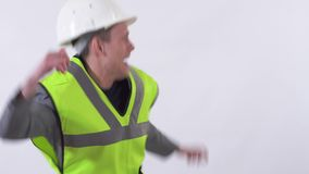 Young handsome man in construction cloth and hat dancing jumping and when saw his boss stop dance and became very stock footage