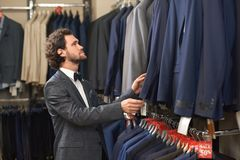 Young handsome man in costume looking for jacket in shop. stock photo