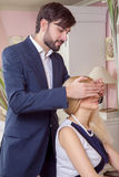 Young handsome man covering the eyes of beautiful surprised girlfriend and make her to guess who is there. Royalty Free Stock Images