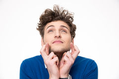 Young handsome man with crossed fingers. Over white background Stock Image
