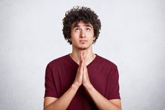Young handsome man with curly dark hair prays with hands together. Teenager dresses casual maroon t shirt, with hope on face, stock images