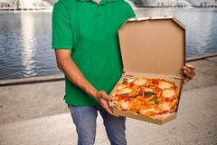 Young handsome man delivering pizza to a customer royalty free stock images