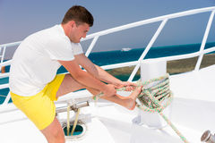 Young handsome man diligently fixes rope on yacht at a sunny sum. Mer day, beautiful sea on background royalty free stock photography