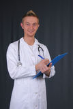 Young handsome man doctor on grey background. Young handsome man doctor write Stock Images