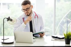 young Handsome man Doctor with stethoscope working with laptop c royalty free stock photography