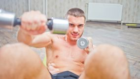Young handsome man doing a curl for abdominals. With dumbbells in his hands. Strength training of abdominal muscles, aerobic royalty free stock photo