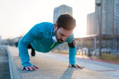 Young handsome man doing push ups outdoors. Young handsome man doing push up training outdoors Stock Photo