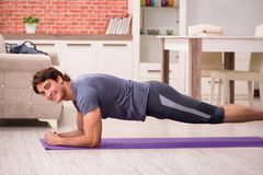 The young handsome man doing sport exercises at home. Young handsome man doing sport exercises at home stock images
