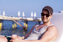 Young handsome man drinking cocktail on the beach Stock Photos