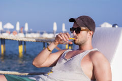 Young handsome man drinking cocktail on the beach Royalty Free Stock Photography