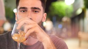 Young man drinking cocktail outside at night. Young handsome man drinking cocktail outside at night sitting at bar table in a summer day in city stock video