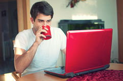 Young handsome man drinking coffe by notebook Royalty Free Stock Photo