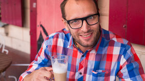 Young handsome man drinking coffee in a cafe indoors. Stock Photo