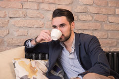 Young handsome man drinking coffee espresso Royalty Free Stock Images