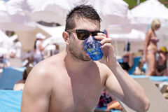 Young handsome man drinking cold jin  at the beach Royalty Free Stock Photo