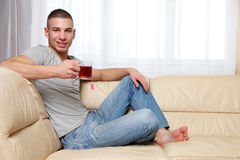 Young handsome man drinking a cup of tea Royalty Free Stock Images