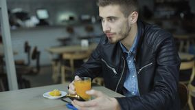 Young handsome man drinks a juice and using smartphone in cafe 4K.  stock footage