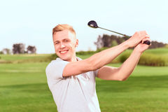 Young handsome man driving ball towards Stock Images