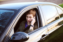 Young handsome man driving car and speaking on mobil Stock Photos