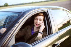 Young handsome man driving car and speaking on mobile phone Royalty Free Stock Photos