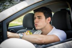 Young man driving his car while eating food Royalty Free Stock Photography
