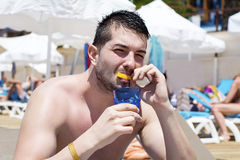 Young handsome man eating fresh lemon  at the beach Stock Image