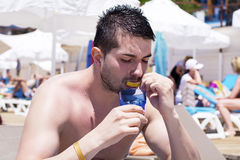 Young handsome man eating fresh lemon  at the beach Royalty Free Stock Photography