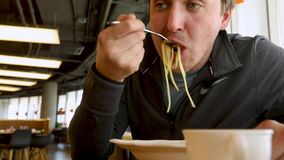 Young handsome man eating spaghetti stock video footage