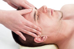 Young handsome man enjoying the facial massage Stock Photos