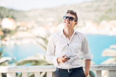 Young handsome man enjoying stay at luxury resort hotel with panoramic view on the sea. Smiling business man using his smartphone options at a earned tropical stock images
