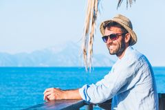 Young handsome man enjoying the view. At the beach bar Royalty Free Stock Photo