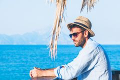 Young handsome man enjoying the view. At the beach bar Stock Images