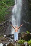 Handsome man at waterfall. Young handsome man enjoying waterfall in the tropics Stock Image