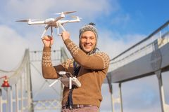A young handsome man of European appearance launches a drone in the background of a blue sky on a bridge in winter. royalty free stock photos