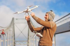 A young handsome man of European appearance launches a drone in the background of a blue sky on a bridge in winter. royalty free stock images