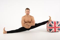 Young handsome man and exercises. Training and relaxation. Stretching and split stock photography