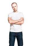 Young handsome man with folded arms in white t-shirt. Vertical portrait of a young handsome man with folded arms in white t-shirt and blue jeans isolated on Stock Photography