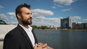 Young handsome man with full-beard hipster talks to camera - city in background stock video footage
