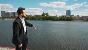 Young handsome man with full-beard hipster talks to camera - city in background stock video