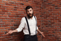 Young handsome man gesturing smoking cigar over brick background. Royalty Free Stock Photo