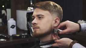 Young handsome man getting his beard trimmed by a professional barber. Close up of a handsome young man smiling while professional barber trimming his beard with stock video footage