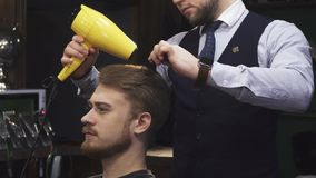 Young handsome man getting his hair dried by a barber stock photo