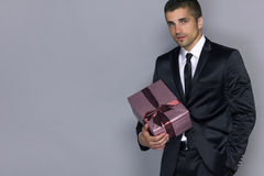 Young handsome man with a gift. Young handsome man in a suit and tie with a gift Stock Images