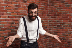 Young handsome man in glasses gesturing over brick background. Stock Photo