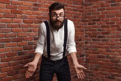 Young handsome man in glasses gesturing over brick background. Royalty Free Stock Photography