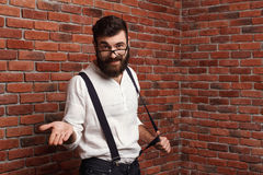 Young handsome man in glasses gesturing over brick background. Royalty Free Stock Photos