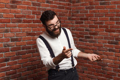 Young handsome man in glasses laughing over brick background. Stock Photos