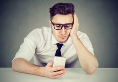 Young man procrastinating with social network. Young handsome man in glasses using phone looking distracted while sitting at table royalty free stock photo