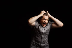 Young handsome man grab his head, shouting over black background. Royalty Free Stock Image