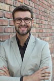 Young handsome man with great smile wearing fashion eyeglasses against brick wall urban background Stock Photos